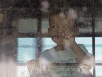 An immigrant child looks out from a U.S. Border Patrol bus leaving as protesters block the street outside the U.S. Border Patrol Central Processing Center Saturday, June 23, 2018, in McAllen, Texas. Additional law enforcement officials were called in to help control the crowd and allow the bus to move. …