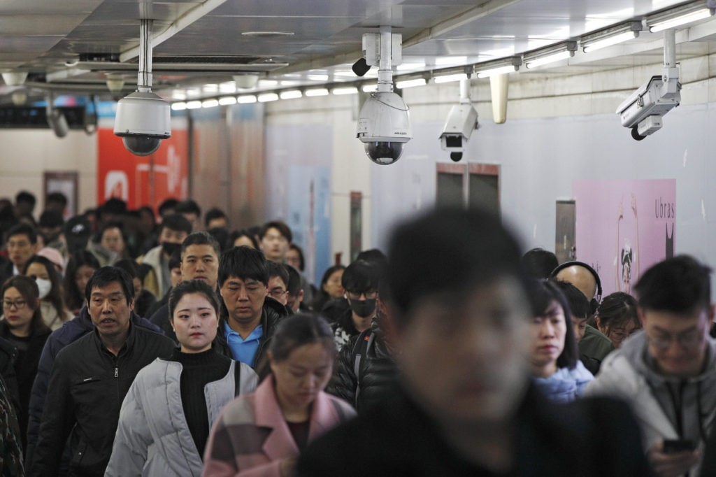 "Commuters walk by surveillance cameras installed at a walkway in between two subway stations in Beijing, Tuesday, Feb. 26, 2019. Chinese government has using the facial recognition to monitor people for it ""social credit"" system. Millions of people in China has blocked from buying plane tickets last year under a controversial ""social credit"" system which part of efforts by President Xi Jinping's government to use data-processing and other technology to tighten control over society. (AP Photo/Andy Wong)"