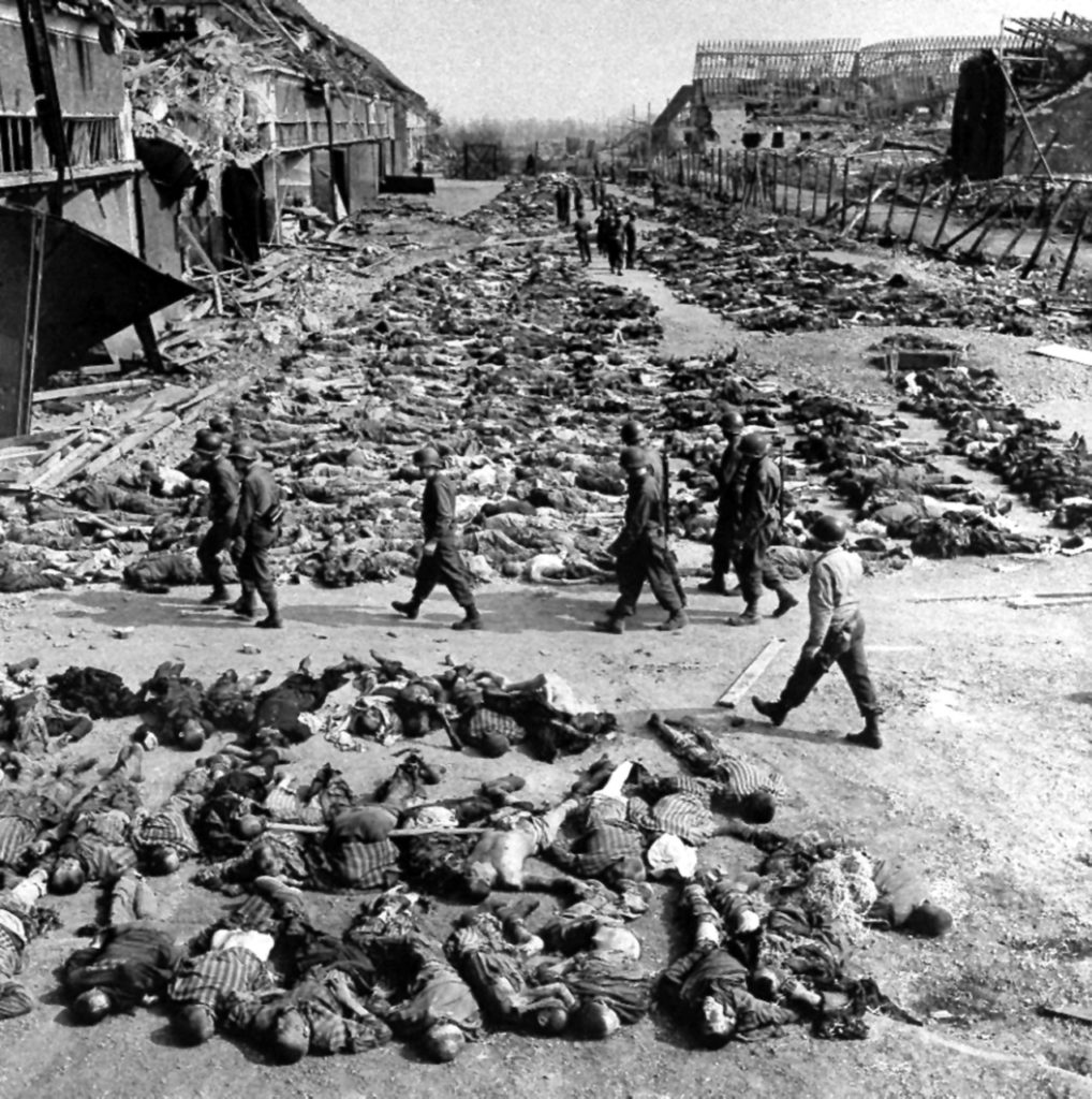 In this image provided by the U.S. Army Signal Corps, American soldiers walk by row after row of corpses lying on the ground beside barracks at the Nazi concentration camp at Nordhausen, Germany, April 17, 1945. The camp is located about 70 miles west of Leipzig. As the camp was liberated on April 12, the U.S. Army found more than 3000 unburied bodies, and a handful of survivors.(AP Photo/U.S. Army Signal Corps)