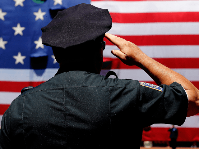 A police officer salutes during the National Anthem before the first game of a doubleheader between the Baltimore Orioles and the Boston Red Sox at Fenway Park on July 5, 2014 in Boston, Massachusetts. (Photo by Jim Rogash/Getty Images)