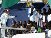"An official wearing a protective suit gestures towards migrants as they sit on the deck of the Italian Coast Guard vessel ""Diciotti"" in the Sicilian port of Catania, on August 23, 2018, as they wait to disembark following a rescue operation at sea. - The Diciotti vessel rescued the migrants …"