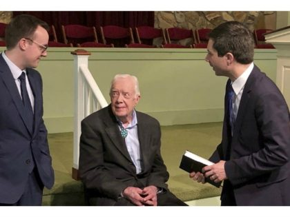 Democratic presidential candidate Pete Buttigieg and his husband, Chasten, speak with former President Jimmy Carter on Sunday in Plains, Georgia. | Paul Newberry/AP Photo
