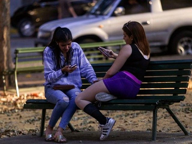 Locals check their mobile phones in a WiFi connectivity area, during a power outage in Caracas on March 9, 2019. - Venezuela President Nicolas Maduro claimed that a new cyber attack had prevented authorities from restoring power throughout the country following a blackout on March 7 that caused chaos. The …