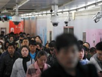"Commuters walk by surveillance cameras installed at a walkway in between two subway stations in Beijing, Tuesday, Feb. 26, 2019. Chinese government has using the facial recognition to monitor people for it ""social credit"" system. Millions of people in China has blocked from buying plane tickets last year under a …"