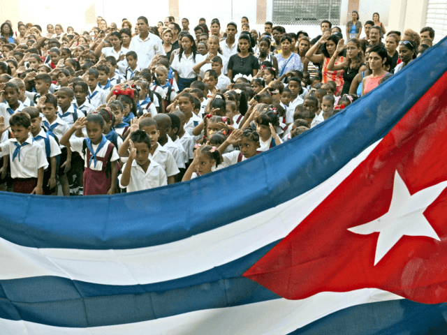 "Cuban school children salute the national flag 03 September 2002 at the ""Juramento de Baragua"" elementary school in La Habana. This particular school was part of Fidel Castro's restoration project of 437 schools and construction of 344 schools to reach the standards of the National Education System. AFP PHOTO/Adalberto ROQUE …"