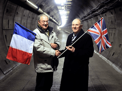 Former workers holding their national flags, French Philippe Cozette (L) and British Graham Fagg, who dug the last meters of the Eurotunnel before the junction, shake hands on February 10, 2014 in the maintenance tunnel, near Coquelles, northern France, 20 years after the event. AFP PHOTO PHILIPPE HUGUEN (Photo credit …