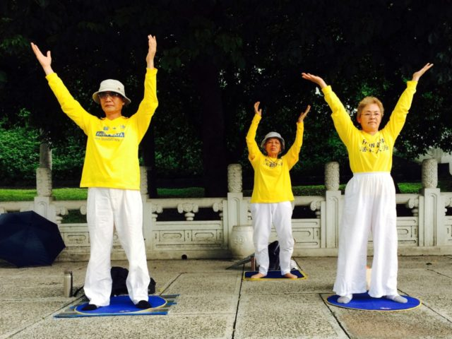"In this Saturday, June 13, 2015 photo, people practice exercises of Falun Gong, a type of qigong exercise, near a sign reading ""Falun Dafa [another name for Falun Gong] is good"" outside the National Palace Museum in Taipei, Taiwan. The Chinese government announced Thursday, June 11, 2015 that former security …"