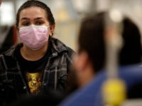 In this Jan. 10, 2018 photo, Torrey Jewett looks on as her roommate Donnie Cardenas recovers from the flu at the Palomar Medical Center in Escondido, Calif. Cardenas, a San Diego County resident, said he was battling a heavy cough for days before a spike his temperature sent him into …