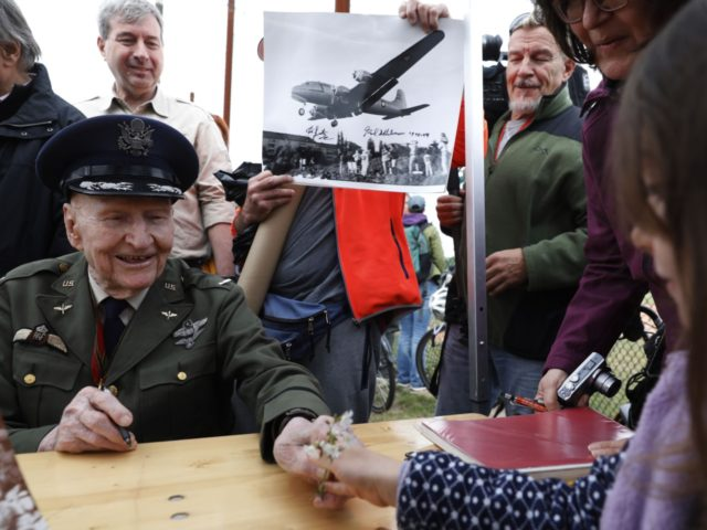 Former Berlin Airlift pilot Gail Halvorsen from the US (L) receives flowers from a girl during a ceremony at the Tempelhofer Feld, a former airfield in Berlin, on May 11, 2019. - The Berlin Braves sports club dedicated their baseball and softball fields to Gail Halvorsen on the sidelines of …