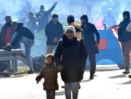An Asian migrant woman with child, walks down the road, in the vicinity of Maljevac border crossing near Northern-Bosnian town of Velika Kladusa, on October 24, 2018. - Illegal migrants gathered near the border crossing in an attempt to cross into neighboring Croatia. Officers of Bosnian border police and Croatian …