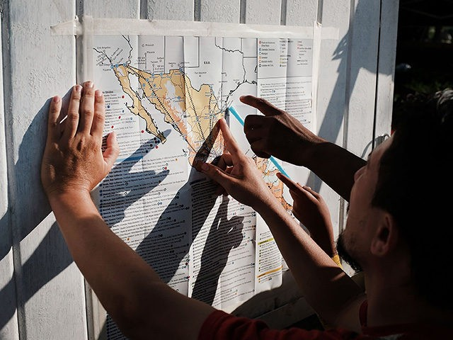SANTIAGO NILTEPEC, MEXICO - OCTOBER 29: Some of the thousands of Central American migrants look at a map after arriving into the small town of Santiago Niltepec on October 29, 2018 in Santiago Niltepec, Mexico. Following a break on Sunday, the migrants, many of them fleeing violence in their home …