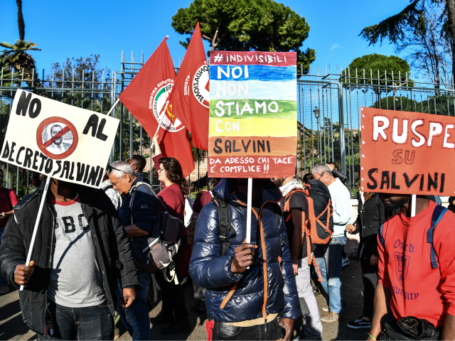 "People, including employees of the country's social and reception centers and members of anti-racism associations, march during a demonstration against the government's social politics, its recent decree restricting the right to asylum, and against racism on November 10, 2018 in downtown Rome. - The placards read (From L) ""No to …"