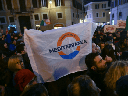 "Demontrators hold a flag reading ""Savin Humans - Mediterranea"" during a gathering organized by local human rights associations in support of the 47 migrants including minors, stranded aboard the Dutch-flagged rescue vessel Sea Watch 3, in front of Italian parliament, in central Rome on January 28, 2019. - Save the …"