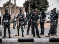 Nigerian police monitor an area where All Progressives Congress Party (APC) supporters are celebrating after initial results were released by the Nigerian Independent National Electoral Commission (INEC) in Kano, on February 25, 2019, two days after general elections. - Nigeria's main opposition on February 25 accused the ruling party of …