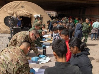 EL PASO, TX - MARCH 22: In this handout image provided by the U.S. Customs and Border Protection Office of Public Affairs - Visual Communications Division, U.S. Border Patrol agents, including members of U.S. Border Patrol's BORSTAR teams (in tactical uniforms) provide food, water and medical screening to scores of …