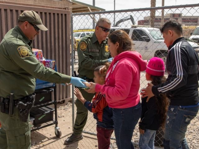 Border Patrol agents providing food and drinks to migrants in an El Paso migrant family processing center. (Photo by Mani Albrecht/U.S. Customs and Border Protection via Getty Images)