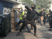 Protesters throw projectiles from behind a baricade during clashes with police on the sidelines of a May Day demonstration in Paris, on May 1, 2019. - Paris riot police fired teargas as they squared off against hardline demonstrators among tens of thousands of May Day protesters, who flooded the city …