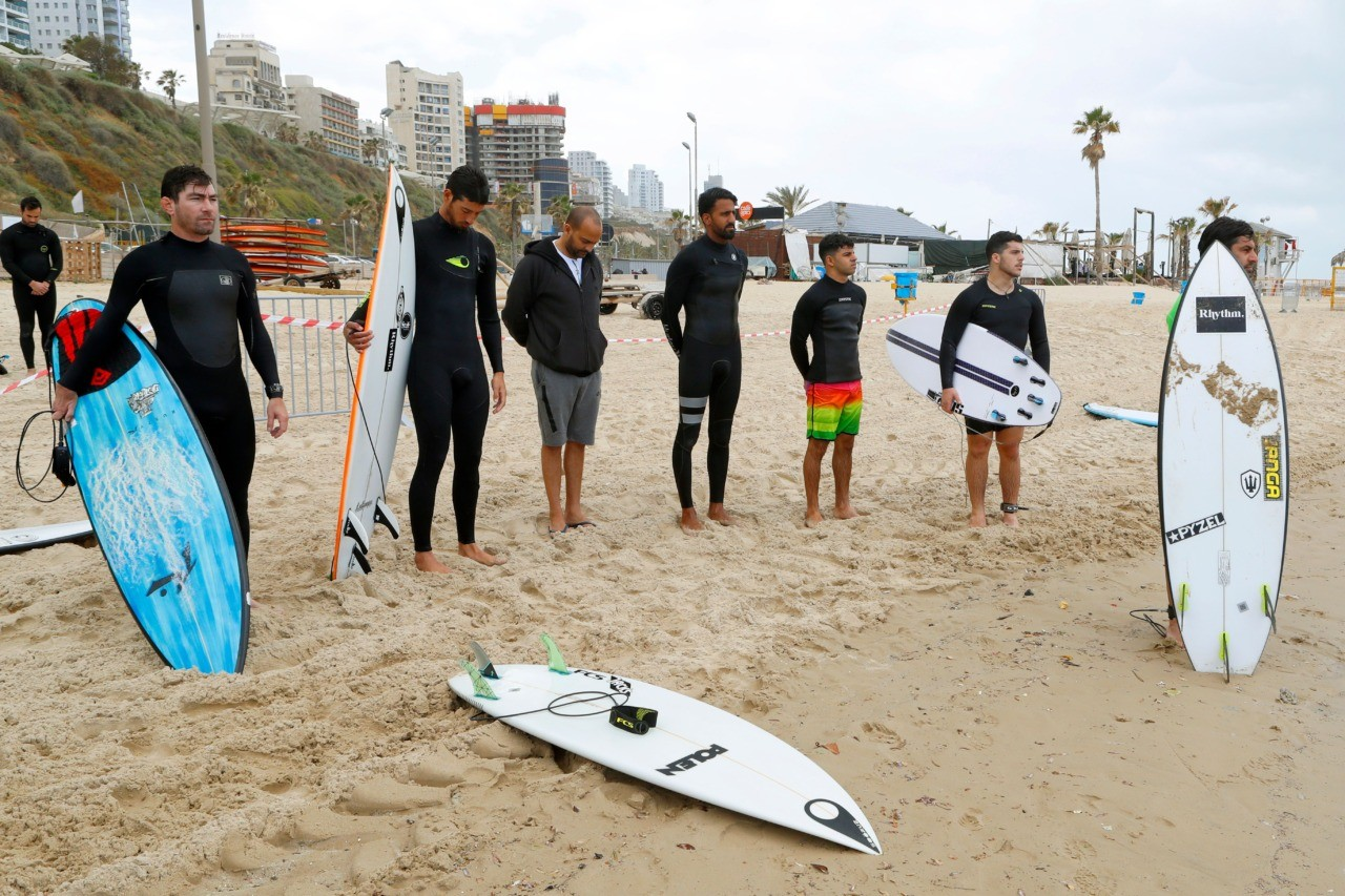 Israeli surfers stand still during two minutes of silence at the Kontiki Beach to mark Remembrance Day (or Memorial Day), on May 8, 2019 in the Israeli coastal city of Netanya. - Israel marked its annual day of remembrance for fallen troops and civilians killed in terror attacks, with the country standing at attention for two minutes while sirens wailed. (Photo by JACK GUEZ / AFP) (Photo credit should read JACK GUEZ/AFP/Getty Images)