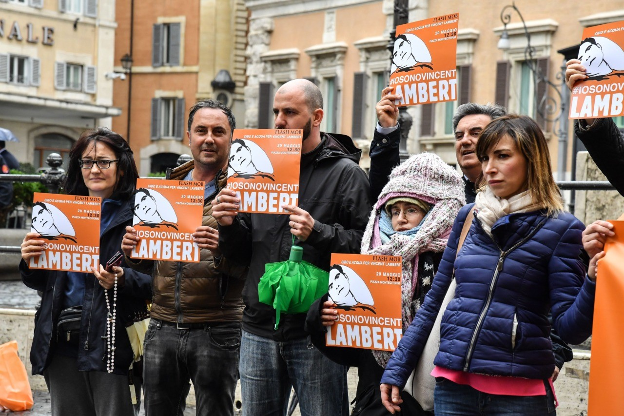 "Italian members of the support committee of French quadriplegic Vincent Lambert, hold a banner reading ""#I'm Vincent Lambert"" as they protest in front of Montecitorio, the Italian Parliament, in central Rome, on May 20, 2019. - Vincent Lambert, a quadriplegic man who has been in a vegetative state for the last decade, currently in Sebastopol hospital where doctors began switching off the life support. The dispute over the fate of Vincent Lambert has split his own family and even become a subject of political tension in France ahead of the weekend's European elections. (Photo by Andreas SOLARO / AFP) (Photo credit should read ANDREAS SOLARO/AFP/Getty Images)"
