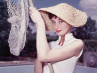 Portrait of Belgian-born American actress Audrey Hepburn (1929 - 1993) as she wears a peculiar hat and sleeveless blouse and holds a pool cleaning net beside a dry swimming pool, early 1950s. (Photo by Hulton Archive/Getty Images)