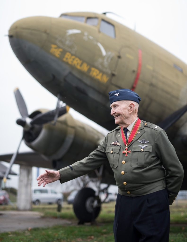 "Veteran of the US Air Force and so-called ""candy bombers"" pilot Gail Halvorsen poses in front of a military transport aircraft at the airport in Frankfurt am Main, central Germany, on November 21, 2016. / AFP / dpa / Boris Roessler / Germany OUT (Photo credit should read BORIS ROESSLER/AFP/Getty Images)"
