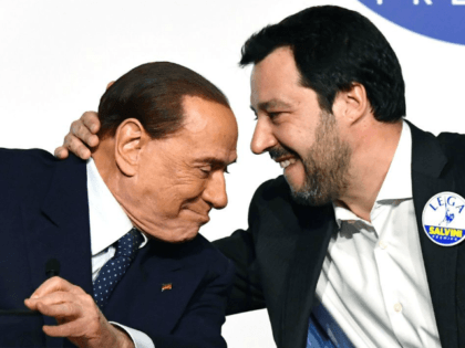 Leader of far-right party the League Matteo Salvini (R) embraces Head of the centre-right Forza Italia (Go Italy) Silvio Berlusconi during a joint press conference with leader of far-right party Brothers of Italy (unseen) at the Tempio di Adriano in Rome on March 1, 2018. Silvio Berlusconi's rightwing coalition, which …