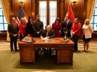 "Missouri Gov. Mike Parson signed an abortion bill into law Friday, banning abortions at eight weeks of pregnancy and asserting that the state is a ""sanctuary of life."""