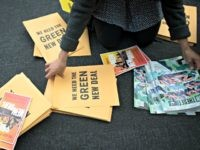 A volunteer prepares information packets for The Road to the Green New Deal Tour final event at Howard University in Washington, Monday, May 13, 2019. Presidential candidates Sen. Bernie Sanders, I-Vt., and Rep. Alexandra Ocasio-Cortez, D-N.Y., will address the rally. (AP Photo/Cliff Owen)
