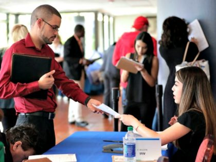 FILE- In this Jan. 30, 2018, file photo, an employee of Aldi, right, takes an application from a job applicant at a JobNewsUSA job fair in Miami Lakes, Fla. On Thursday, Jan. 3, 2019, payroll processor ADP reports how many jobs private employers added in December. (AP Photo/Lynne Sladky