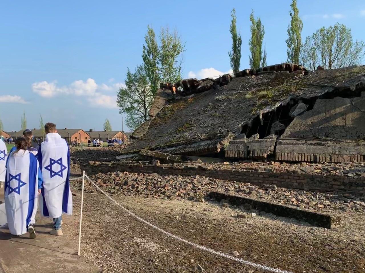 Participants walk by the ruins of a crematorium at Birkenau