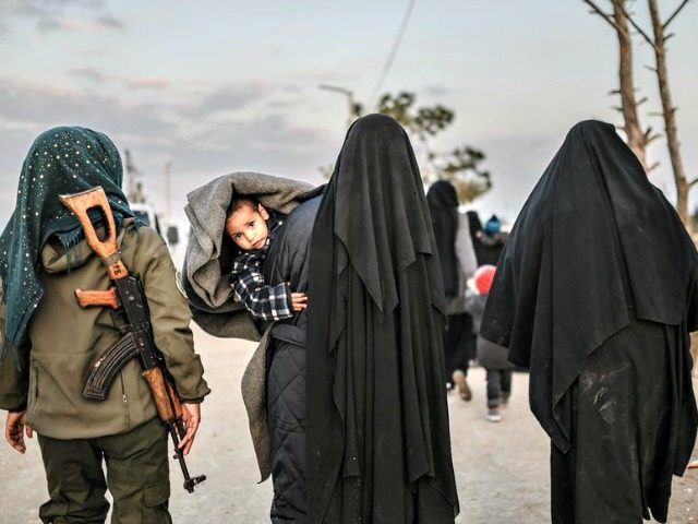 Veiled women reportedly associated with ISIS walk under the supervision of a female fighter from the Syrian Democratic Forces in northeastern Syria on Sunday. Over the weekend, President Trump demanded European allies repatriate their citizens captured as ISIS fighters. Bulent Kilic /AFP/Getty Images