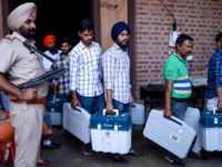An Indian Punjab Police personnel stands guard as election officials carry Electronic Voting Machines (EVM) and Voter-Verified Paper Audit Trail (VVPAT) leaving a distribution centre in Amritsar on May 18, 2019, on the eve of the 7th and final phase of India's general election. (Photo by NARINDER NANU / AFP) …