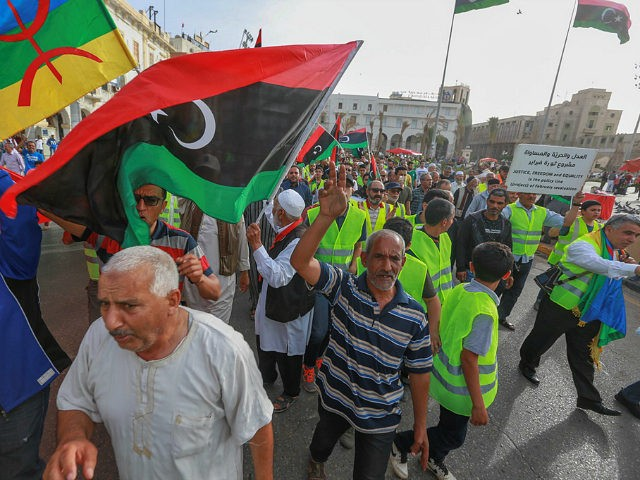"""Libyans call for an end to fighting during a demonstration against strongman Khalifa Haftar in the capital Tripoli's Martyrs Square on May 3, 2019. - Haftar's forces in early April launched their assault on Tripoli, seat of the internationally-recognised Government of National Accord, pledging to clear the capital of """"mercenaries …"""