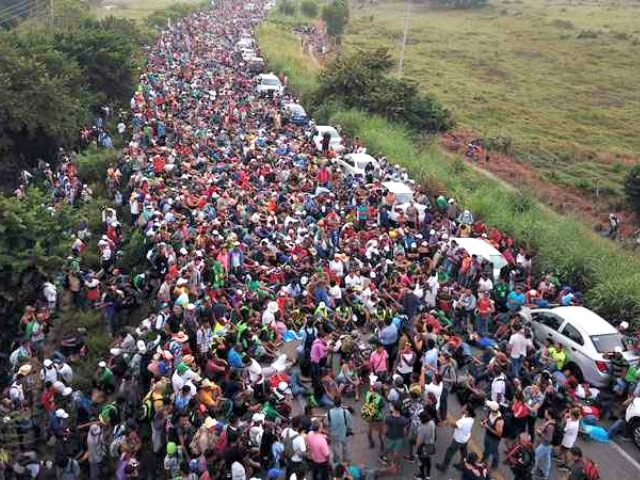 Members of a US-bound migrant caravan stand on a road after federal police briefly blocked their way outside the town of Arriaga, Saturday, Oct. 27, 2018. AP Photo/Rodrigo Abd