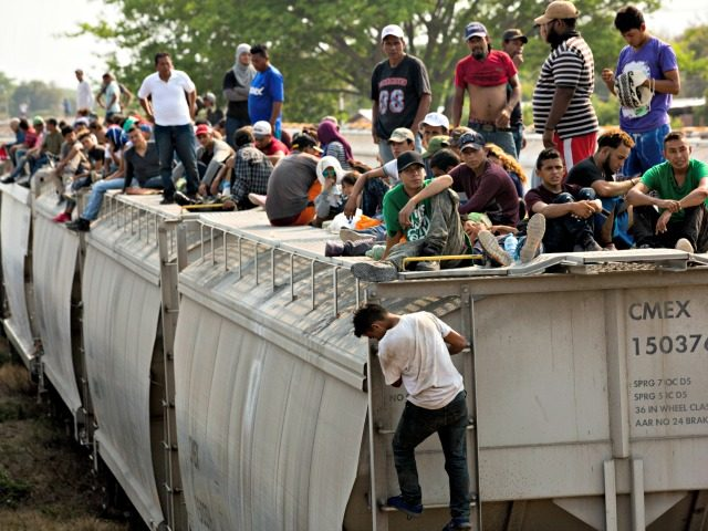 Central American migrants wait on the top of a parked train during their journey toward the US-Mexico border in Ixtepec, Oaxaca state, Mexico, Tuesday, April 23, 2019. The once large caravan of about 3,000 people was essentially broken up by an immigration raid on Monday, as migrants fled into the …