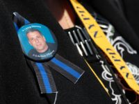 A family member of New York Police Department Officer Anthony D'Erasmo, who died of cancer developed after participating in search and rescue efforts at the World Trade Center following the 9/11 attacks, wears a ribbon in his honor as she arrives to attend the 38th Annual National Peace Officers' Memorial …