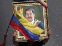 Supporters of Venezuelan President Nicolas Maduro carry a portrait of him during a rally in Caracas, Venezuela, Wednesday, May 1, 2019. Opposition leader Juan Guaidó called for Venezuelans to fill streets around the country Wednesday to demand President Nicolás Maduro's ouster. Maduro is also calling for his supporters to rally.(AP …