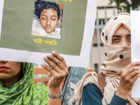In this photo taken on April 12, 2019 Bangladeshi women hold placards and photographs of schoolgirl Nusrat Jahan Rafi at a protest in Dhaka, following her murder by being set on fire after she had reported a sexual assault. - A schoolgirl was burned to death in Bangladesh on the …