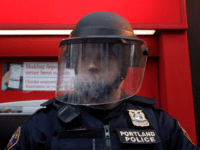 A policeman in riot gear defends a Bank of America as protesters march past various banks November 17, 2011 in Portland, Oregon. The Occupy Portland movement joined the nationwide N17 protests today, targeting downtown banks. (Photo by Natalie Behring/Getty Images)