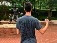 David Belnap, a sophomore at the University of North Carolina at Charlotte, displays a t-shirt in Charlotte, N.C., Wednesday, May 1, 2019, in support of Riley Howell, a classmate who was killed while confronting a gunman inside a classroom on Tuesday. Howell was one of two people killed in the …