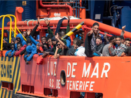 Migrants wave aboard a Salvamento Maritimo sea search and rescue agency vessel after they were rescued from a boat stranded in the Strait of Gibraltar during a rescue operation with the Spanish Guardia Civil on September 8, 2018.