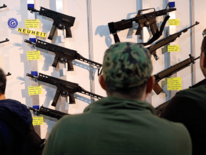 Visitors look at semi-automatic shotguns displayed on a wall during the 45th edition of the Arms Trade Fair, in Lucerne, on March 29, 2019. - Switzerland, where gun culture has deep roots, has managed to avoid the charged national debates surrounding firearm ownership that have consumed other countries. But in …