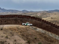 TOPSHOT - A Border Patrol officer sits inside his car as he guards the US/Mexico border fence, in Nogales, Arizona, on February 9, 2019. (Photo by Ariana Drehsler / AFP) (Photo credit should read ARIANA DREHSLER/AFP/Getty Images)