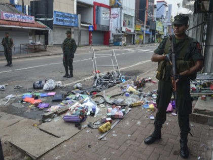 Sri Lankan security personnel stand guard outside a damaged shop after a mob attack in Minuwangoda on May 14, 2019. - A Sri Lankan province north of the capital was under indefinite curfew on May 14 after the first death in anti-Muslim riots in the wake of the Easter terror …