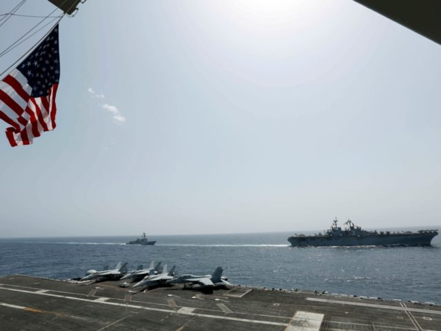 In this Friday, May 17, 2019, photo, released by the U.S. Navy, the amphibious assault ship USS Kearsarge, right, and the Arleigh Burke-class guided-missile destroyer USS Bainbridge, left, are seen from the Nimitz-class aircraft carrier USS Abraham Lincoln as they sail in the Arabian Sea. Commercial airliners flying over the …