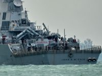 The guided-missile destroyer USS John S. McCain, with a hole on its portside after a collision with an oil tanker, makes its way to Changi naval base in Singapore on August 21, 2017. Ten US sailors were missing and five injured after their destroyer collided with a tanker east of …