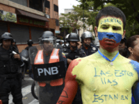 A man with his body painted in the Venezuelan national flag's colors, demonstrates in front of riot police during an opposition demo calling for the armed forces to disobey Venezuelan President Nicolas Maduro near La Carlota Air Base in Caracas on May 4, 2019. - Venezuelan President Nicolas Maduro called …