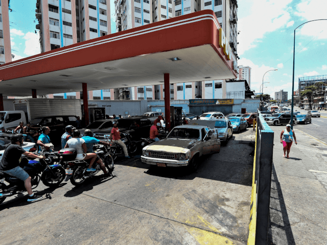 """People queue at a gas station in Caracas, on March 10, 2019, during a massive power outage. - National Assembly leader Juan Guaido said Sunday he will ask the Venezuelan legislature to declare a """"state of alarm"""" in order to request international aid amid a massive power outage. (Photo by …"""