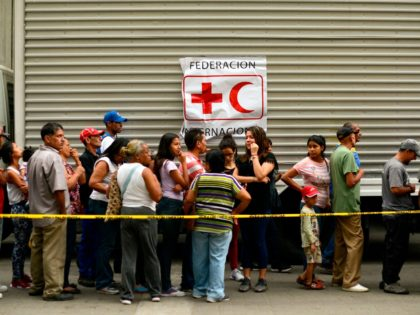 TOPSHOT - People queue to receive drums to collect water and water purification tablets from members of the Venezuelan Red Cross in Caricuao neighborhood in Caracas, Venezuela, on April 16, 2019. - The first shipment of Red Cross humanitarian aid arrived in crisis-wracked Venezuela on Tuesday following approval from President …