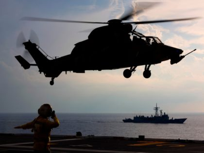 Royal Australian Navy sailor Leading Seaman Aviation Support Gabriella Hayllar marshalls an Australian Army ARH Tiger Armed Reconaissance Helicopter from HMAS Canberra as HMAS Newcastle maintains station nearby.